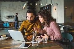 Varón joven del inconformista y ordenador portátil de trabajo femenino junto en café Fotografía de archivo