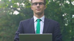 Varón joven en el traje que se sienta en la hierba que mecanografía en el ordenador portátil, empleo independiente metrajes