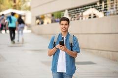 Varón joven feliz del estudiante que manda un SMS en su teléfono elegante en ciudad moderna Imágenes de archivo libres de regalías