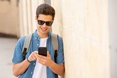 Varón joven feliz del estudiante que manda un SMS en su teléfono elegante en ciudad moderna Imagen de archivo