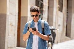 Varón joven feliz del estudiante que manda un SMS en su teléfono elegante en ciudad moderna Fotografía de archivo libre de regalías