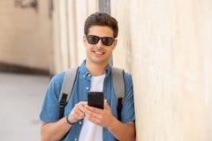 Varón joven feliz del estudiante que manda un SMS en su teléfono elegante en ciudad moderna Fotos de archivo libres de regalías