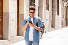 Varón joven feliz del estudiante que manda un SMS en su teléfono elegante en ciudad moderna Foto de archivo libre de regalías