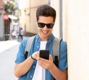 Varón joven feliz del estudiante que manda un SMS en su teléfono elegante en el ci moderno Fotos de archivo libres de regalías