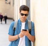 Varón joven feliz del estudiante que manda un SMS en su teléfono elegante en el ci moderno Imagen de archivo