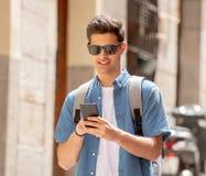 Varón joven feliz del estudiante que manda un SMS en su teléfono elegante en el ci moderno Imágenes de archivo libres de regalías