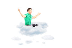 Varón joven feliz que se sienta en una nube y que se separa los brazos Imagen de archivo