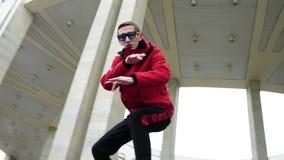 Varón joven hermoso en rap rojos de la chaqueta y de las gafas de sol al lado de columnas del granito almacen de metraje de vídeo