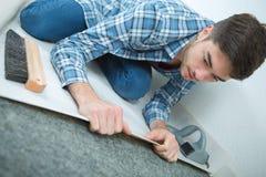 Varón joven que desenrolla el nuevo piso en el emplazamiento de la obra foto de archivo
