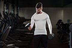 Varón joven que hace ejercicios del bíceps en el gimnasio Fotografía de archivo libre de regalías