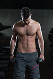 Varón joven que hace ejercicios del bíceps en el gimnasio Foto de archivo libre de regalías