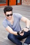 Varón joven que juega a juegos en un smartphone Imagenes de archivo