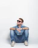 Varón joven que mira para arriba y que se sienta en el piso Imagen de archivo libre de regalías