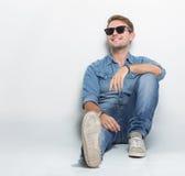 Varón joven que mira para arriba y que se sienta en el piso Fotos de archivo libres de regalías
