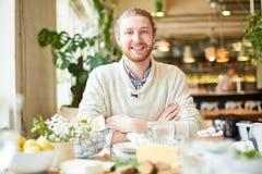Varón joven que sonríe y que mira la cámara en café foto de archivo libre de regalías