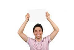 Varón joven que sostiene una paginación en blanco sobre su cabeza Imagen de archivo libre de regalías