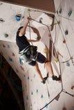 Varón joven que sube para arriba en la pared de la práctica en gimnasio Imágenes de archivo libres de regalías