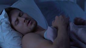 Varón joven que tiene sueños de la ansiedad, hablando en sueño después de día laborable agotador largo metrajes