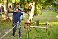 Varón joven que tira un arco en un festival medieval anual, llevado a cabo en el castillo peninsular de Trakai imagenes de archivo