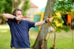 Varón joven que tira un arco en un festival medieval anual, llevado a cabo en el castillo peninsular de Trakai fotos de archivo