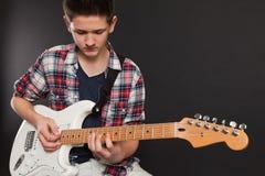 Varón joven que toca la guitarra eléctrica Fotos de archivo libres de regalías