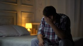 Varón joven solo infeliz que se sienta en la cama que mira la foto, desintegración, esposa perdida almacen de metraje de vídeo