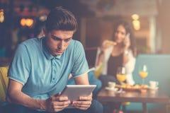 Varón joven usando la tableta digital en oficina de lanzamiento moderna Fotografía de archivo libre de regalías