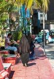 VARÓN, MALDIVAS - NOVIEMBRE, 27, 2016: Mujer en un burqa negro en una calle de la ciudad Copie el espacio para el texto vertical imagenes de archivo