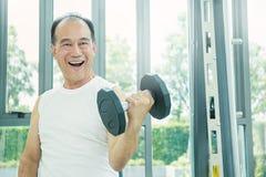 Varón mayor asiático que hace el entrenamiento del peso Imagenes de archivo