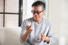 Varón mayor asiático que toma píldoras Imágenes de archivo libres de regalías