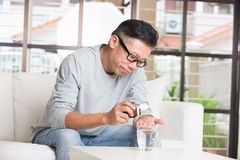 Varón mayor asiático que toma píldoras Fotografía de archivo