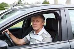 Varón mayor feliz que se sienta en coche en asiento de programa piloto Imágenes de archivo libres de regalías