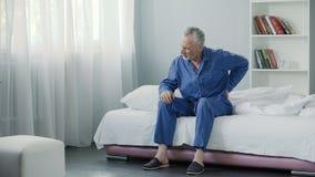 Varón mayor que sufre el dolor de espalda agudo, persona enferma que se levanta de la cama, mañana imagen de archivo libre de regalías