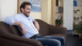 Varón mediados de-envejecido alegre que se sienta en el sofá, disfrutando de su lotería que gana, felicidad fotos de archivo