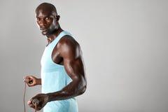 Varón muscular hermoso que presenta con la cuerda de salto foto de archivo