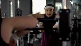 Varón obeso agotado después de entrenamientos en el gimnasio, mirando su reflexión en espejo fotos de archivo libres de regalías