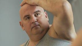 Varón obeso triste que mira su reflexión de espejo y que piensa en problemas almacen de metraje de vídeo