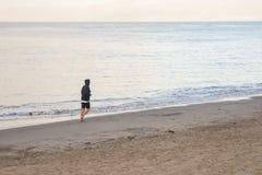 Varón que activa en la playa que va lejos de cámara Fotografía de archivo