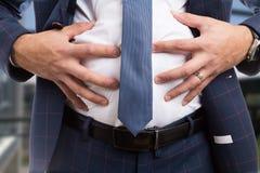 Varón que ase el abdomen hinchado como problema de la indigestión imágenes de archivo libres de regalías