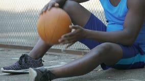 Varón que calienta con la bola de la cesta, para jugadores de equipo que esperan, actividades al aire libre almacen de metraje de vídeo