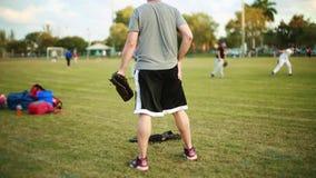 Varón que entrena a niños durante práctica en el campo de béisbol almacen de video