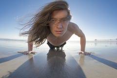 Varón que hace pectorales en la playa foto de archivo libre de regalías