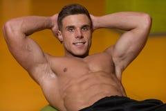 Varón que hace pectorales en un gimnasio Foto de archivo libre de regalías