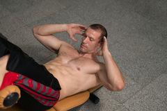 Varón que hace pectorales en un gimnasio Imagen de archivo