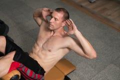 Varón que hace pectorales en un gimnasio Fotografía de archivo