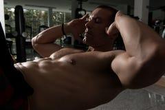 Varón que hace pectorales en un gimnasio Foto de archivo