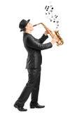 Varón que juega en el saxofón y notas que salen Fotografía de archivo libre de regalías
