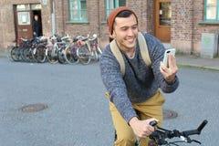 Varón que mira este teléfono celular mientras que monta una bicicleta Fotografía de archivo