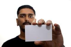Varón que mira fijamente con la tarjeta en blanco aumentada Fotos de archivo libres de regalías