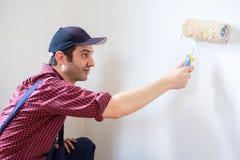 Varón que pinta sus paredes del hogar del blanco con el rodillo imagen de archivo libre de regalías